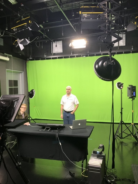 Guy standing in front of a green screen